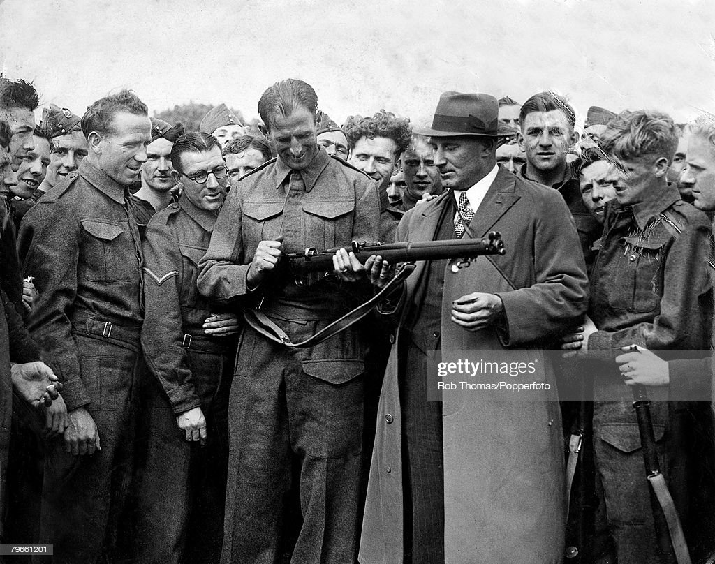 Football, Circa 1940, Liverpool goalkeeper Arthur Riley holding his rifle with Matt Busby (left), one of the many interested onlookers : News Photo