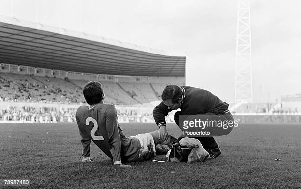 Football Circa 1960's Old Trafford Manchester Manchester United trainer Wilf McGuiness attends to an injured player on the pitch