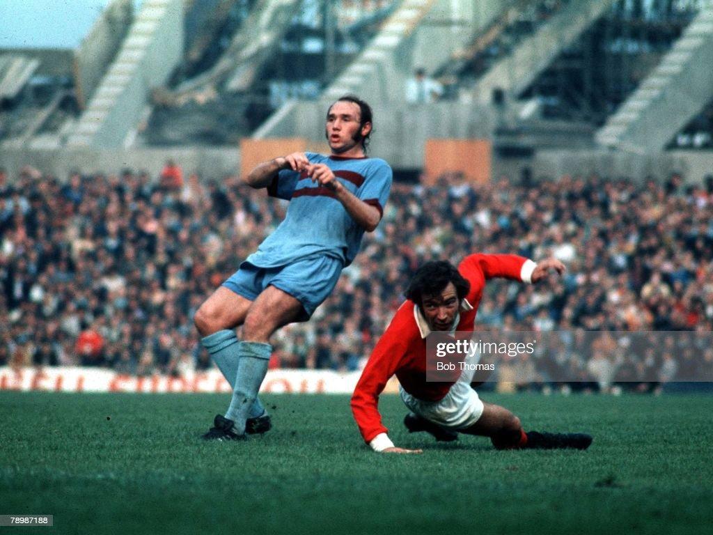 Football, Circa 1970's, Manchester United v West Ham Utd, David Sadler of Man,Utd, is tackled by Bryan 'Pop' Robson