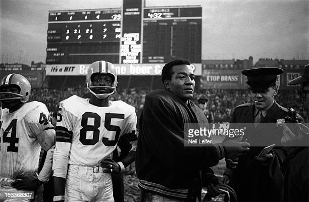 Cleveland Browns Jim Brown on sidelines signing autograph for officer during game vs New York Giants at Yankee Stadium View of Clifton McNeil Bronx...
