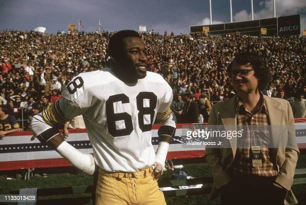 Closeup of Pittsburgh Steelers LC Greenwood on sidelines with Sports Illustrated writer Roy Blount Jr during game CREDIT Walter Iooss Jr