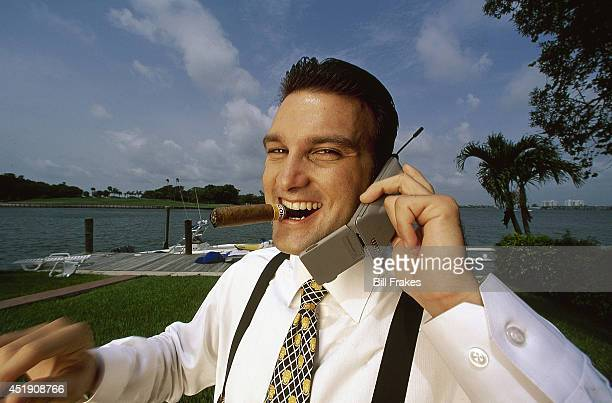Closeup portrait of sports agent Drew Rosenhaus on cellular phone with cigar in mouth during photo shoot. Miami, FL 7/6/1996 CREDIT: Bill Frakes