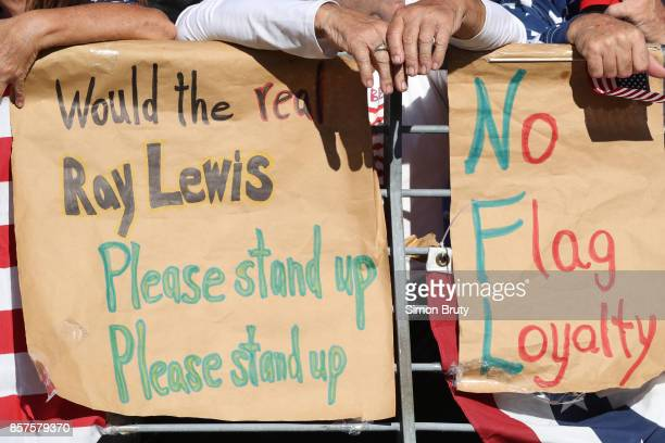 Closeup view of signs in stands that read WOULD THE REAL RAY LEWIS PLEASE STAND UP PLEASE STAND UP and NO FLAG LOYALTY duirng Baltimore Ravens vs...