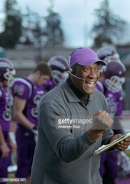 Football coach cheering, wearing headset