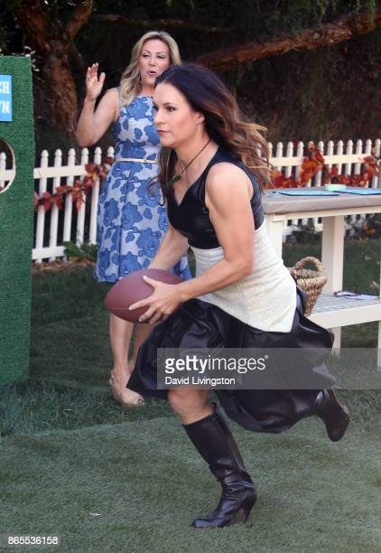 Football coach Dr Jennifer Welter runs with football as TV personality Kym Douglas watches at Hallmark's Home Family at Universal Studios Hollywood...