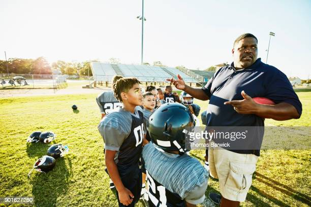 Football coach giving instructions to young players during practice