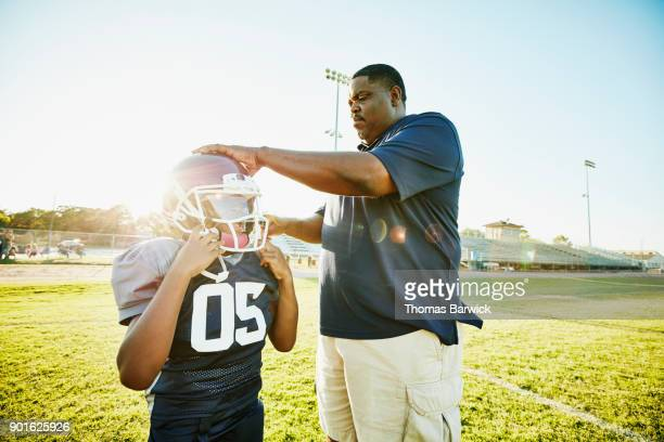 football coach helping young player put on helmet before practice - football bulge stock photos and pictures