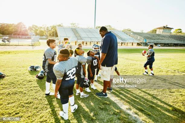 Football coach in discussion with players after football practice