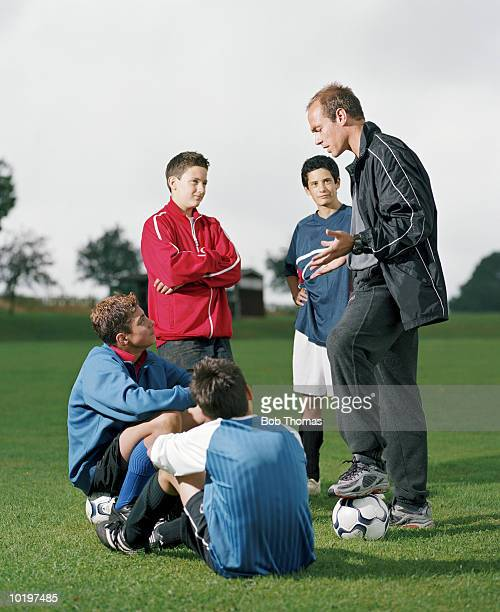 Football coach instructing four boys (12-14)