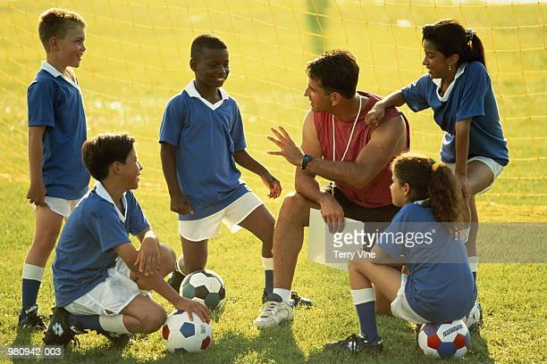 football coach talking to group of children (10-12) - northern european descent stock pictures, royalty-free photos & images