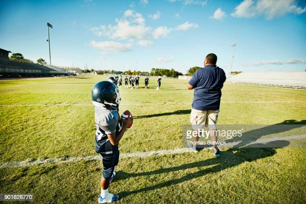 Football coach talking to young players during passing drill on football field