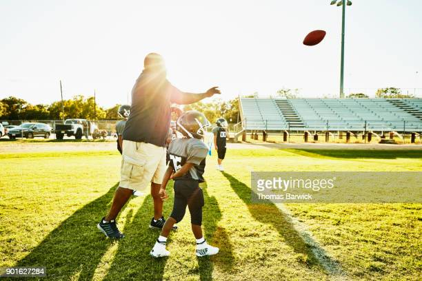 Football coach throwing pass to young players during practice