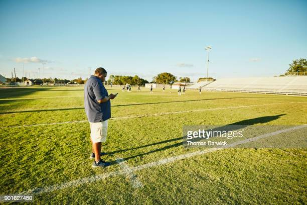 Football coach working on smartphone during practice with young football players