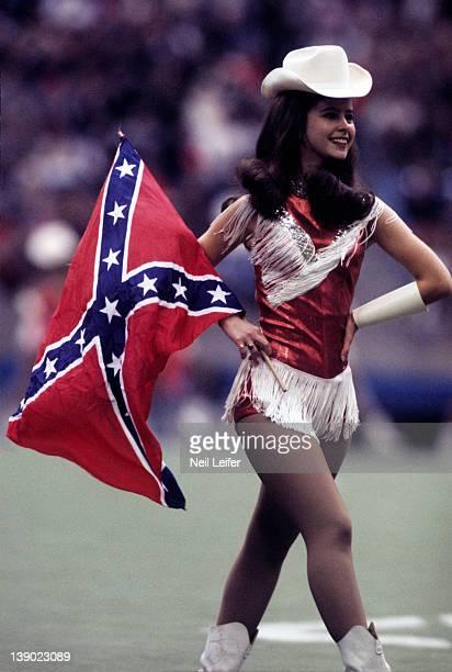 Dallas Cowboys cheerleader holding a Confederate flag during game vs Washington Redskins at Texas Stadium Irving TX 12/9/1972CREDIT Neil Leifer