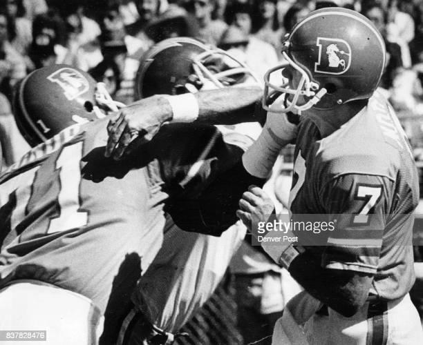 Football Denver Broncos Denver quarterback Craig Morton unloads a pass over a at Mile High Stadium Bronco left tackle Claudie Minor charging Charger...