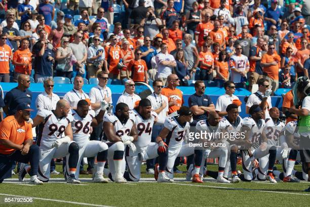 Denver Broncos players kneel and link arms in solidarity during the National Anthem before game vs Buffalo Bills at Ralph Wilson Stadium Buffalo NY...