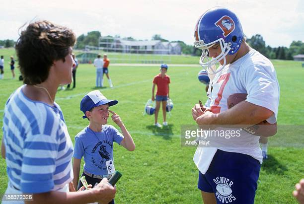 Denver Broncos QB John Elway signing autograph for young fan during practice at University of Northern Colorado Greeley CO CREDIT Andy Hayt