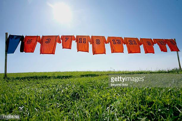 football dresses hanging on clothesline - sports uniform stock pictures, royalty-free photos & images