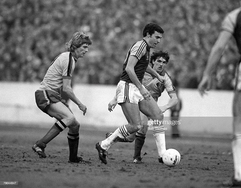 Football. FA Cup 4th Round. Watford, England. 23rd January 1982. Watford 2 v West Ham United 0. West Ham's Trevor Brooking is challenged for the ball by Watford's Ross Jenkins and Jan Lohman. : News Photo