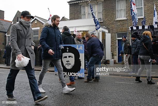 A football fan carries a poster bearing an images of Tottenham Hotspur's Argentinian head coach Mauricio Pochettino as Ernesto 'Che' Guevara ahead of...
