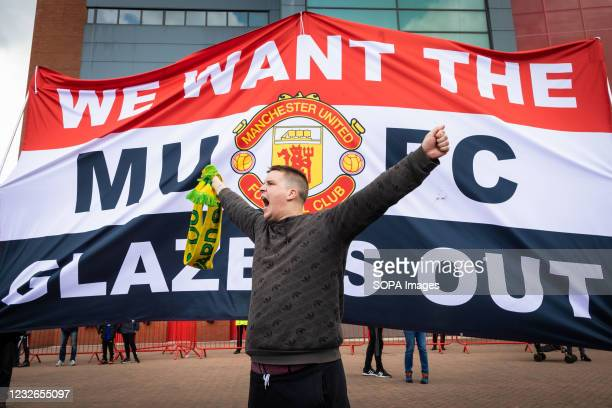 Football fan chants slogans in front of a banner before a protest against the Glazer's ownership of Manchester United.