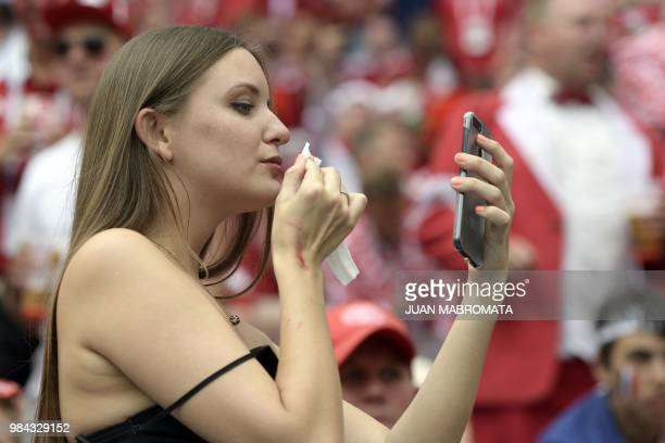 A football fan checks her makeup before the Russia 2018 World Cup Group C football match between Denmark and France at the Luzhniki Stadium in Moscow...
