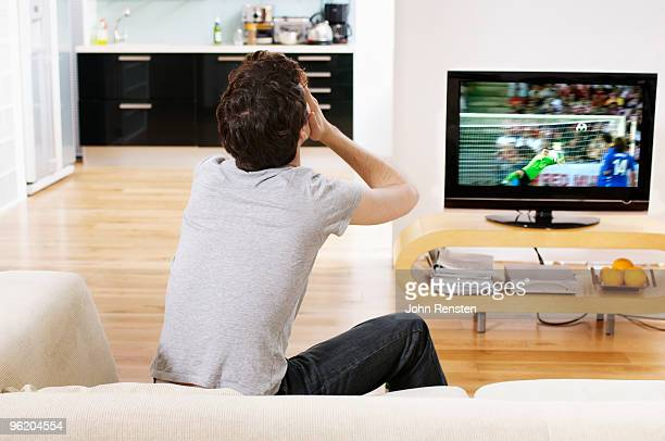 football fan covers eyes as goal scored on tv