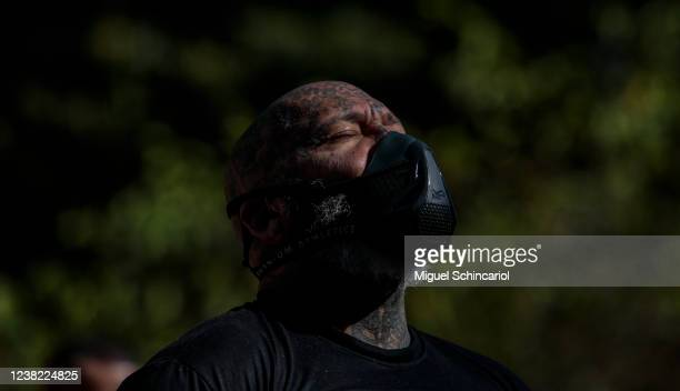 A football fan demonstrator wears a protective mask as clashing with riot police during a protest against President of Brazil Jair Bolsonaro amidst...