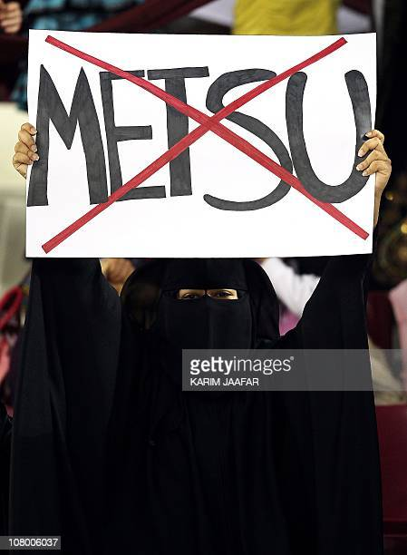 A football fan holds a placard with the crossedout name of Qatar's coach Bruno Metsu during the 2011 Asian Cup group A football match between China...