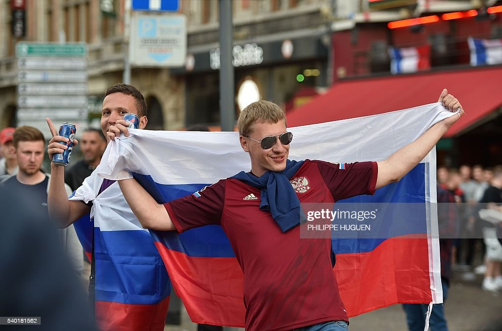 A football fan holds a Russian national flag while others drink beer at the terrace of a bar in Lille, northern France, on June 14, 2016. The bars in downtown Lille will be closed 'at midnight' on June 15 and 16, on the sidelines of the Euro 2016 football tournament matches Russia vs Slovakia in Lille and England vs Wales in Lens, has announced on June 14, 2016 the Prefect of the Nord region, Michel Laland. / AFP / PHILIPPE
