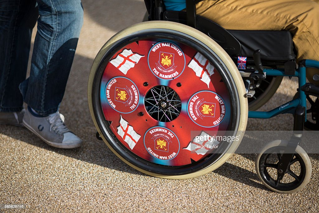 A football fan in a wheelchair decorated with West Ham United markings and England flags arrives to watch West Ham United v NK Domzale at the London Stadium on August 4, 2016 in London, England. West Ham United play for the first time tonight at the former Olympic Stadium, which hosted the London 2012 Games, since moving from their former home at Upton Park.