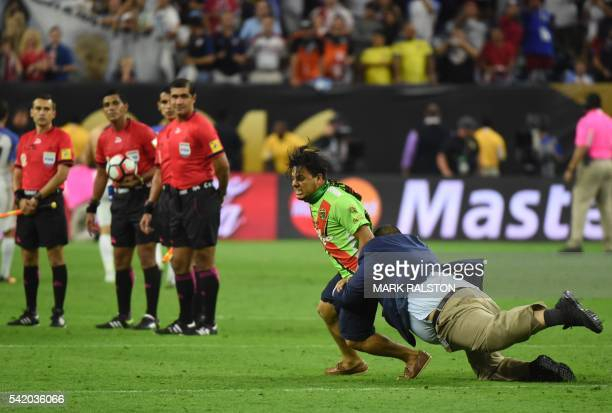 A football fan is tackled by security personnel after stepping onto the field at the end of the Copa America Centenario semifinal football match...