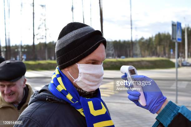 A football fan passes a medical control before the Belarus Championship football match between FC BATE and FC Rukh in the town of Borisov some 70 km...