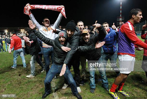 """Football fan performs a """"quenelle"""" as Cannes' supporters celebrate after Cannes won their French Cup football match against Montpellier at the..."""