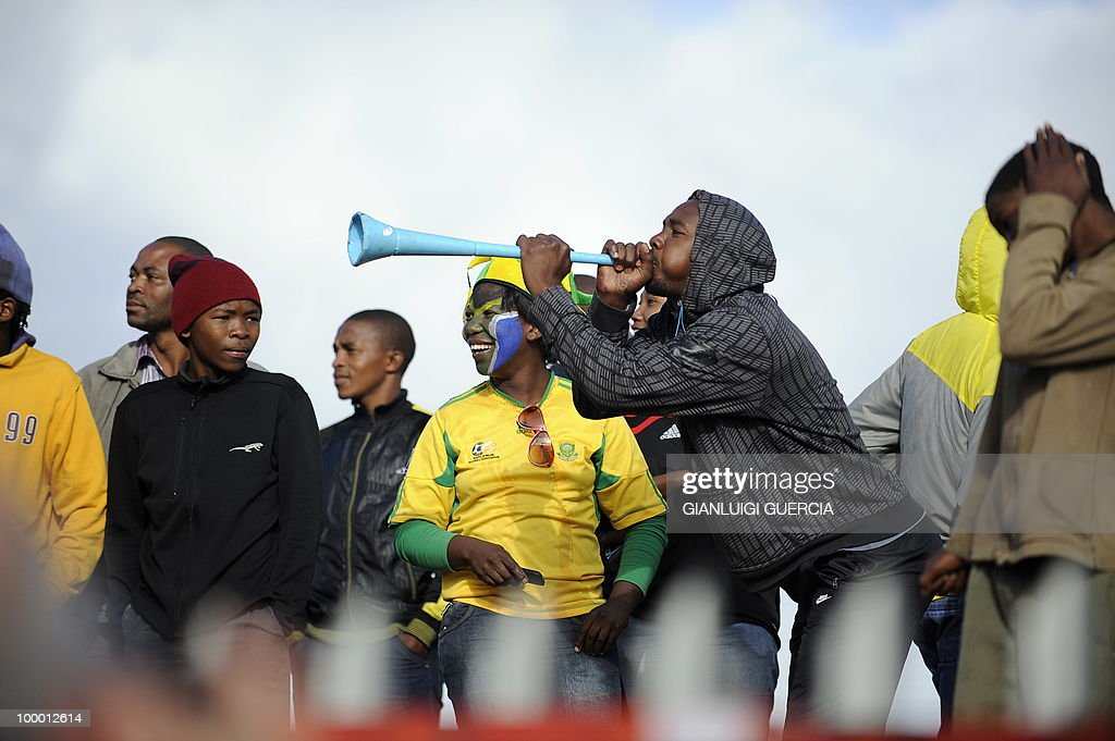 Football fan play the vuvuzela as hundreds of Kayelitsha residents line up as they wait to enter the O.R. Tambo center and see the FIFA World Cup trophy after the unveiling on May 07, 2010 during the kick off of its South African tour in Kayelitsha on the outskirt of Cape Town, South Africa.
