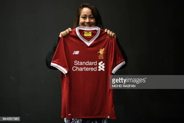 A football fan poses with a 2017 Liverpool jersey during the Malaysia Book of Records event for the most number of jerseys on display of a single...