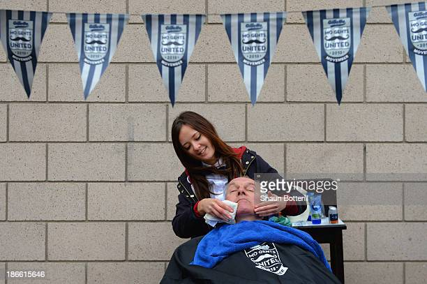A football fan receives a shave in aid of charity 'Movember' outisde the stadium ahead of the Barclays Premier League match between Newcastle United...