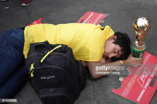 A football fan sleeps off the excitement at the official FIFA Fan Fest at Moscow State University to watch the first World Cup game between Russia...
