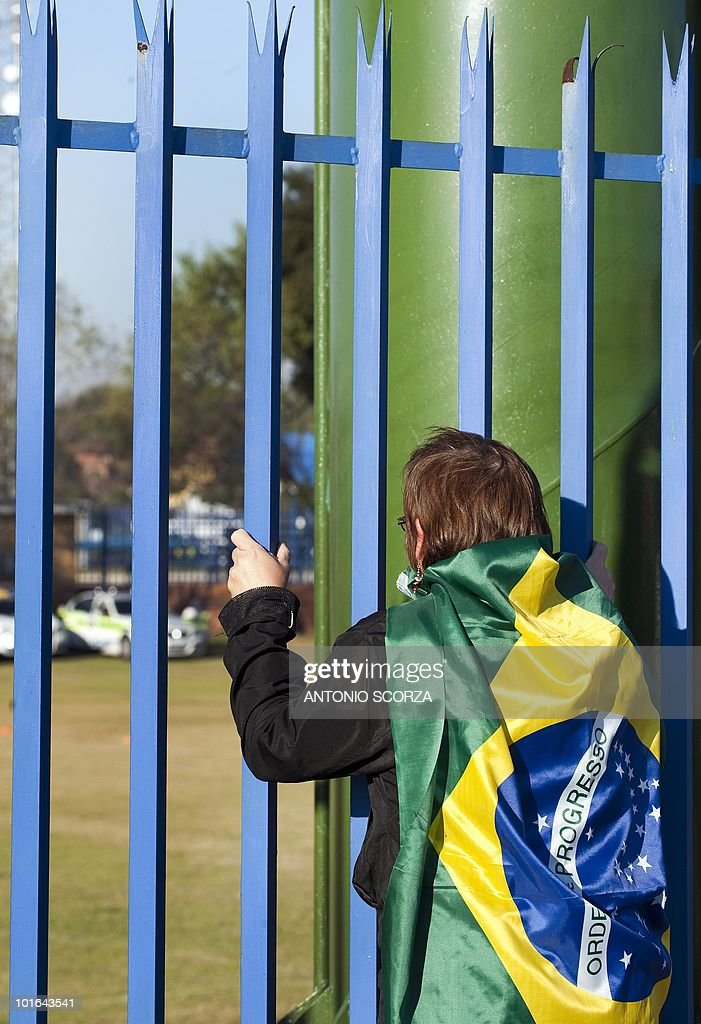 A football fan supporting Brazil looks through the bars surrounding the pitch where the team is holding a training session at Randburg High School on June 5, 2010 in Johannesburg. The team is preparing to compete in the 2010 World Cup football tournament in South Africa.