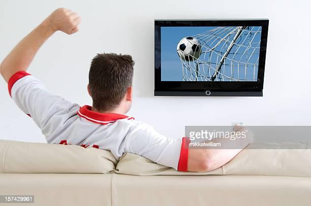 Fußball-fan schaut sich Fußballspiele im Fernsehen oder cheers