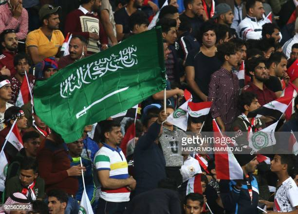 A football fan waves a Saudi Arabian flag during the friendly football match between Iraq and Saudi Arabia at the Basra Sports city stadium in Basra...