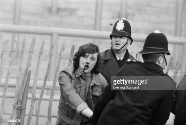 A football fan with a bloodied face accompanied by police officers at the FA Cup Fifth Round match between Chelsea and Crystal Palace at Stamford...