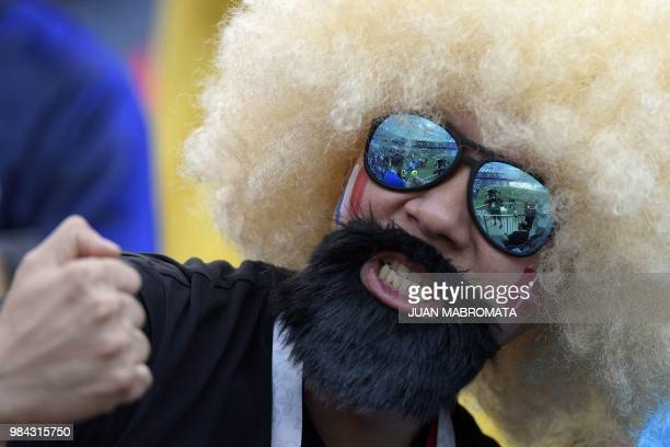 A football fan with a fancy wig and a fake black beard gestures before the Russia 2018 World Cup Group C football match between Denmark and France at...