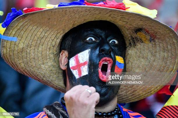 TOPSHOT A football fan with his face painted with the flags of England and Colombia cheers before the Russia 2018 World Cup round of 16 football...