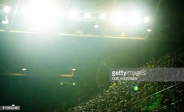 Football fans are seen under the floodlights during the UEFA Champions League first leg football match between Borussia Dortmund and Real Madrid at...