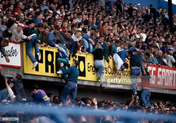 Football fans being lifted to safety from the central pens in the Leppings Lane stand allocated to Liverpool supporters during the start of the FA...