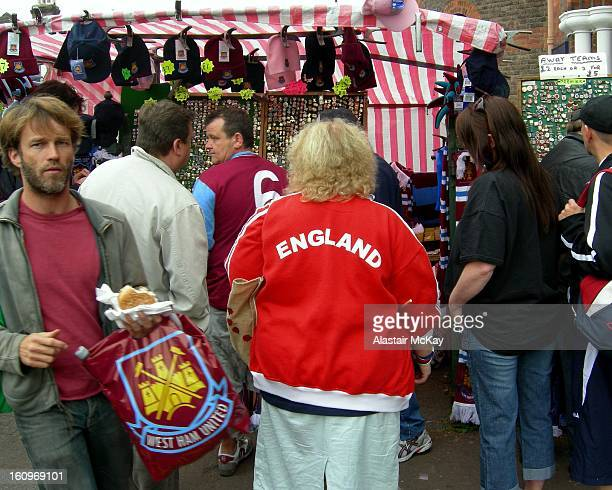 Football fans browsing outside West Ham's Upton Park , London. A woman fan wears an England tracksuit top, while a man has a carrier bag from the...