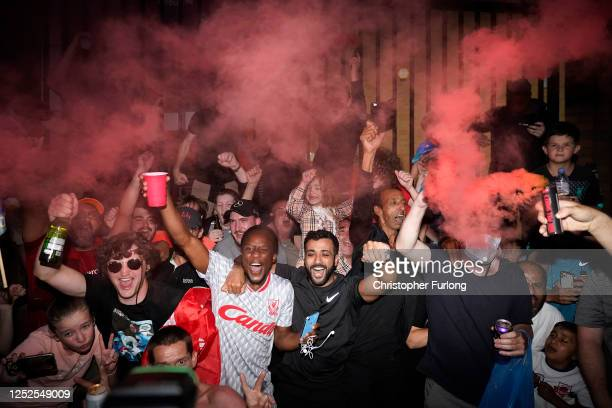 Football fans celebrate at Anfield Stadium as Liverpool FC win the Premier League title after Chelsea beat Manchester City tonight ensuring Liverpool...