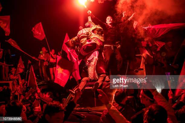 Football fans celebrate in front of My Dinh Stadium as Vietnam win the first ASEAN Football Federation Suzuki Cup in 10 years after 32 aggregate win...