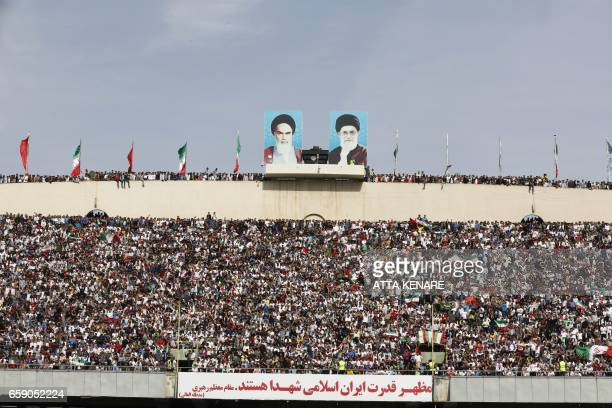 TOPSHOT Football fans cheer during the 2018 World Cup qualifying football match between Iran and China at the Azadi Stadium in Tehran on March 28...